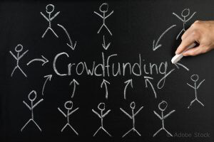 Close-up Of Person Drawing Arrow Direction With Crowd Funding Text On Blackboard