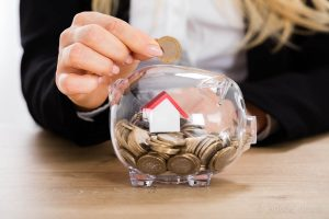 Businesswoman Inserting Coin In Transparent Piggybank Filled With Coins And House Model. Property Investment Concept