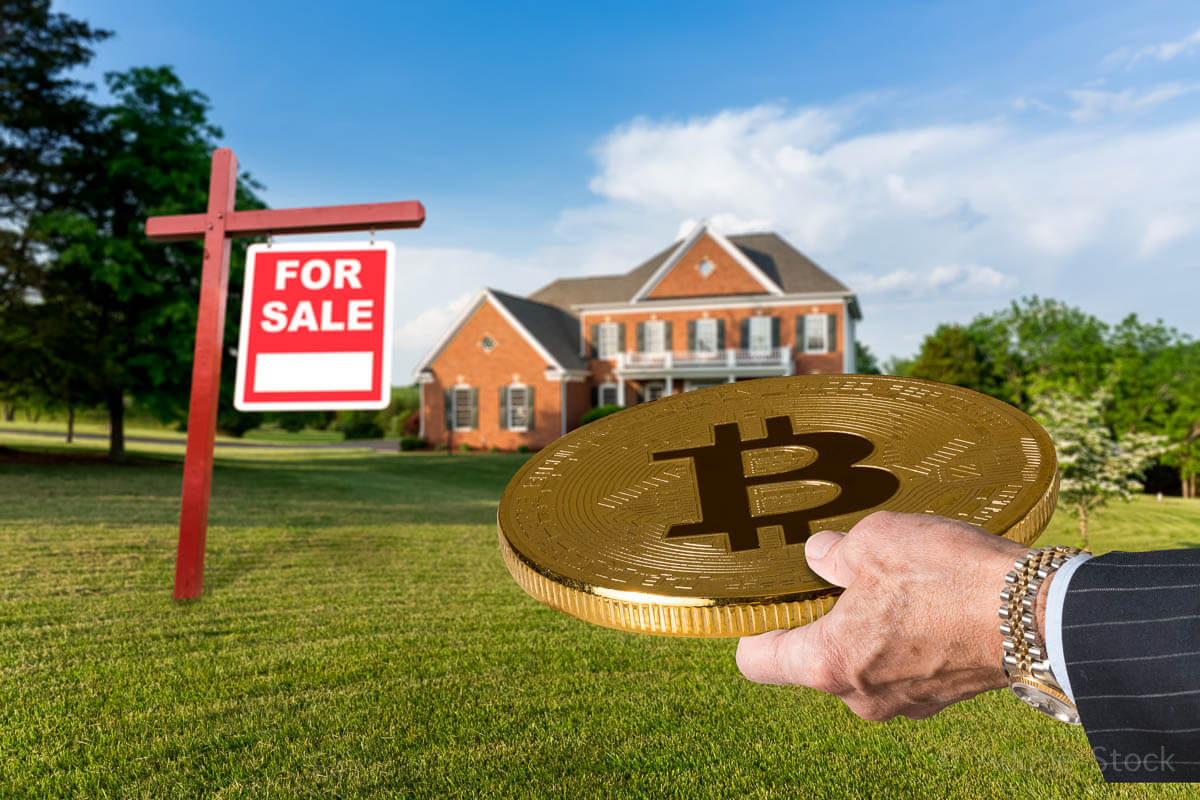 Businessman hand offering Bitcoin to buy house