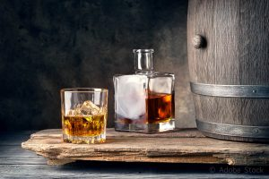 Glass of whiskey with ice decanter and barrel on wooden table