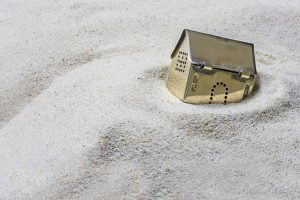 built on sand, small golden model house sinking into the sand, concept of risk in real estate financing, or investing in gold, selected focus, Copy Space