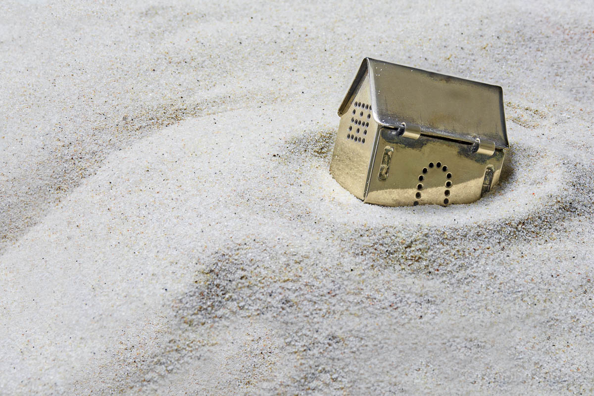 small golden model house sinking into the sand, concept of risk